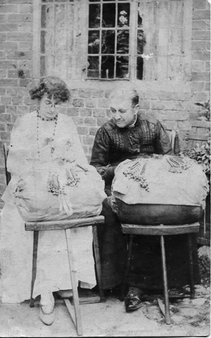 Two women sitting outside with lace pillows